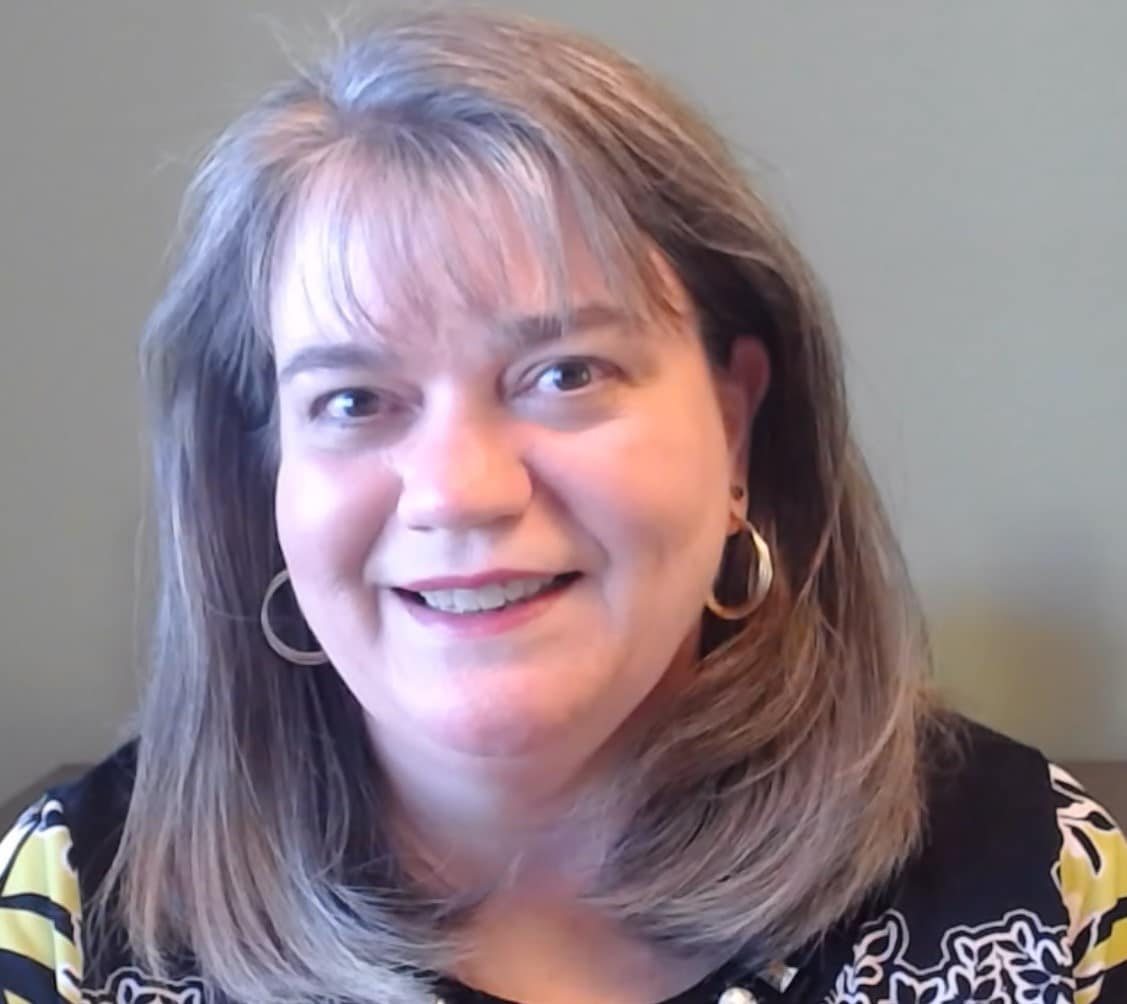 Photo of Karen Kilgo, President and CEO of Flat Rock Homes, Care Center, and Community Services. She is looking at the camera and smiling. Her hair is down, she has on silver hoop earrings, and a black patterned top.